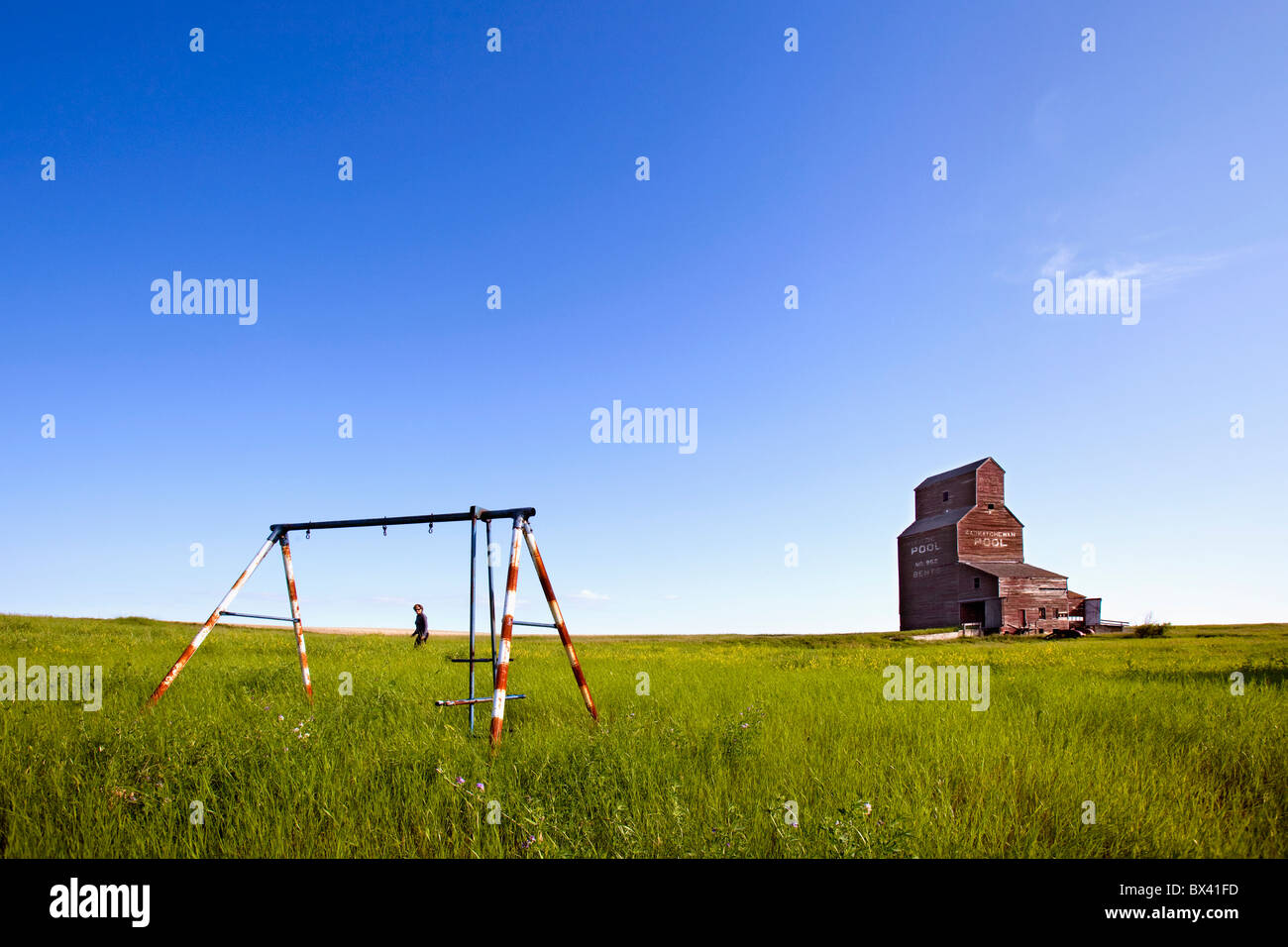 A Man Walking Through A Field With An Old Swing Set And An Old Grain Elevator; Bents, Saskatchewan, Canada - Stock Image