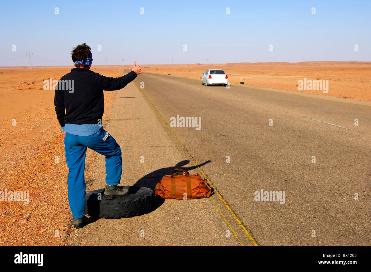 Desperate Woman standing with a travelling bag next to a flat tyre at the edge of a country road trying to stop - Stock Image