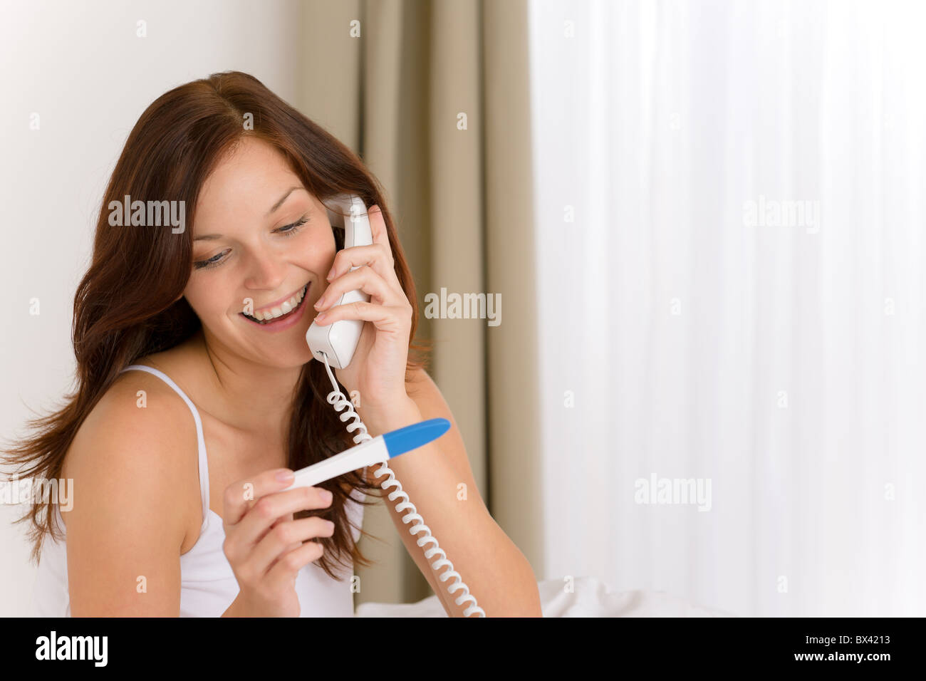 Pregnancy test - happy woman on phone, positive result - Stock Image