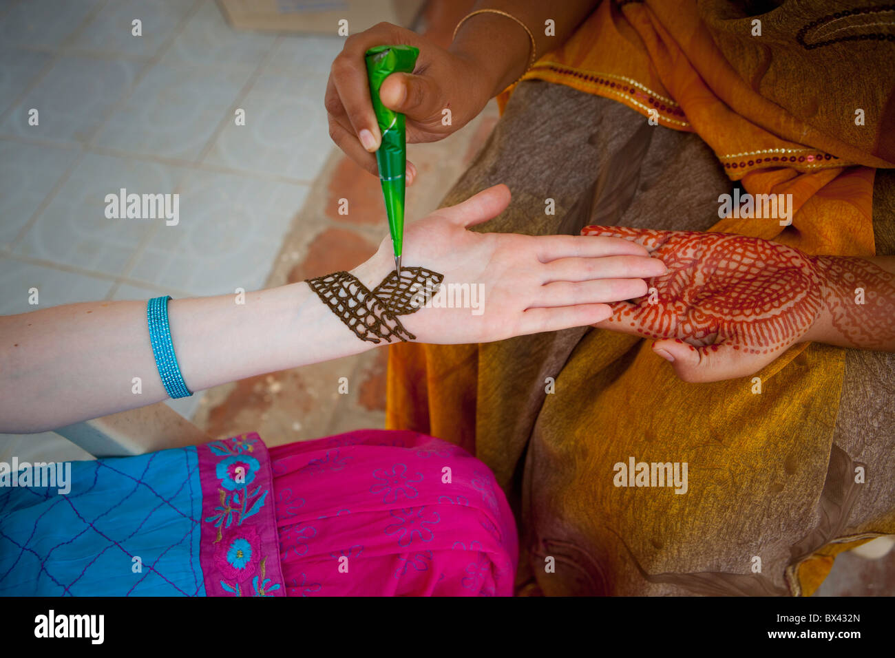 A Woman Doing Henna Painting On Another Woman's Arm; Sathyamangalam, Tamil Nadu, India - Stock Image