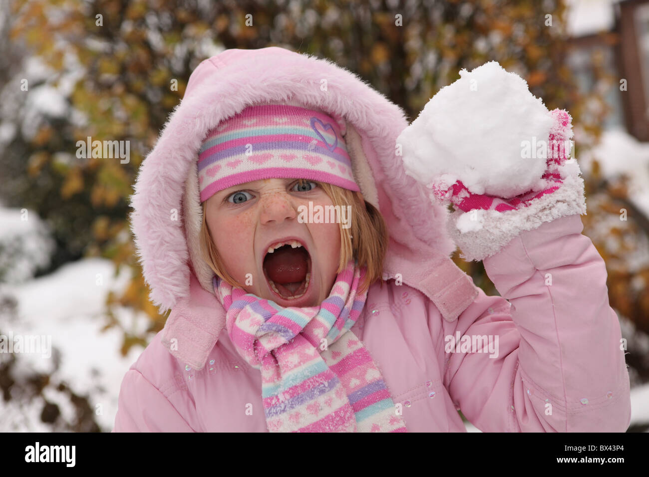 A young cheeky girl ready to throw a snowball - Stock Image
