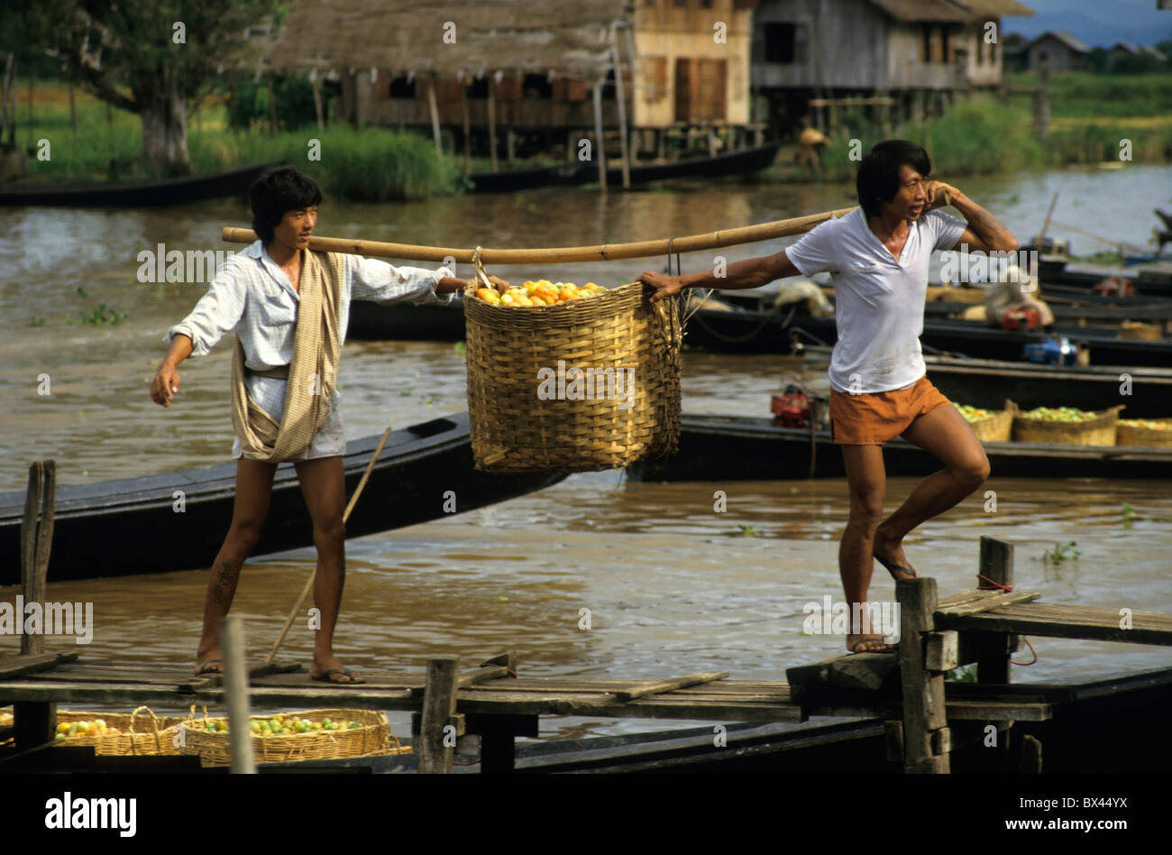 Two men disembarking from a boat carrying baskets full of tomatoes on Inle Lake, Nyaung Shwe, Burma. - Stock Image