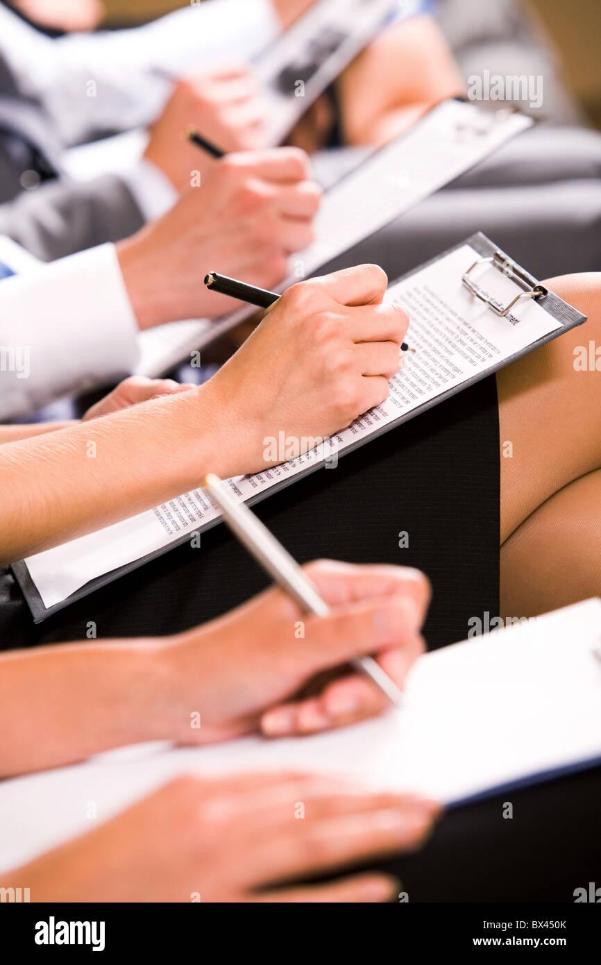 Row of business people making notes at seminar - Stock Image