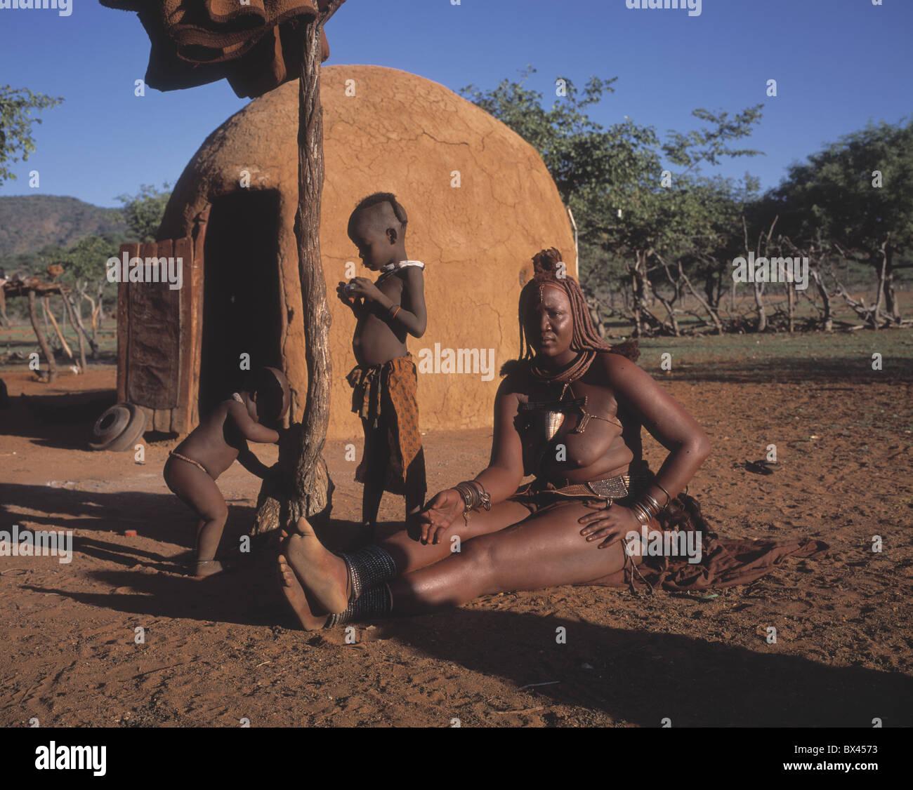 Himba-Ovahimba trunk tribe woman hut children Kraal Kral Kaokoveld Namibia Africa - Stock Image