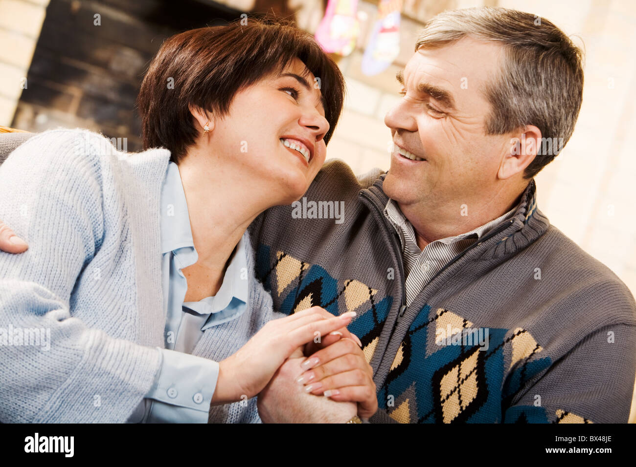 Portrait of happy senior couple looking at each other with smiles - Stock Image