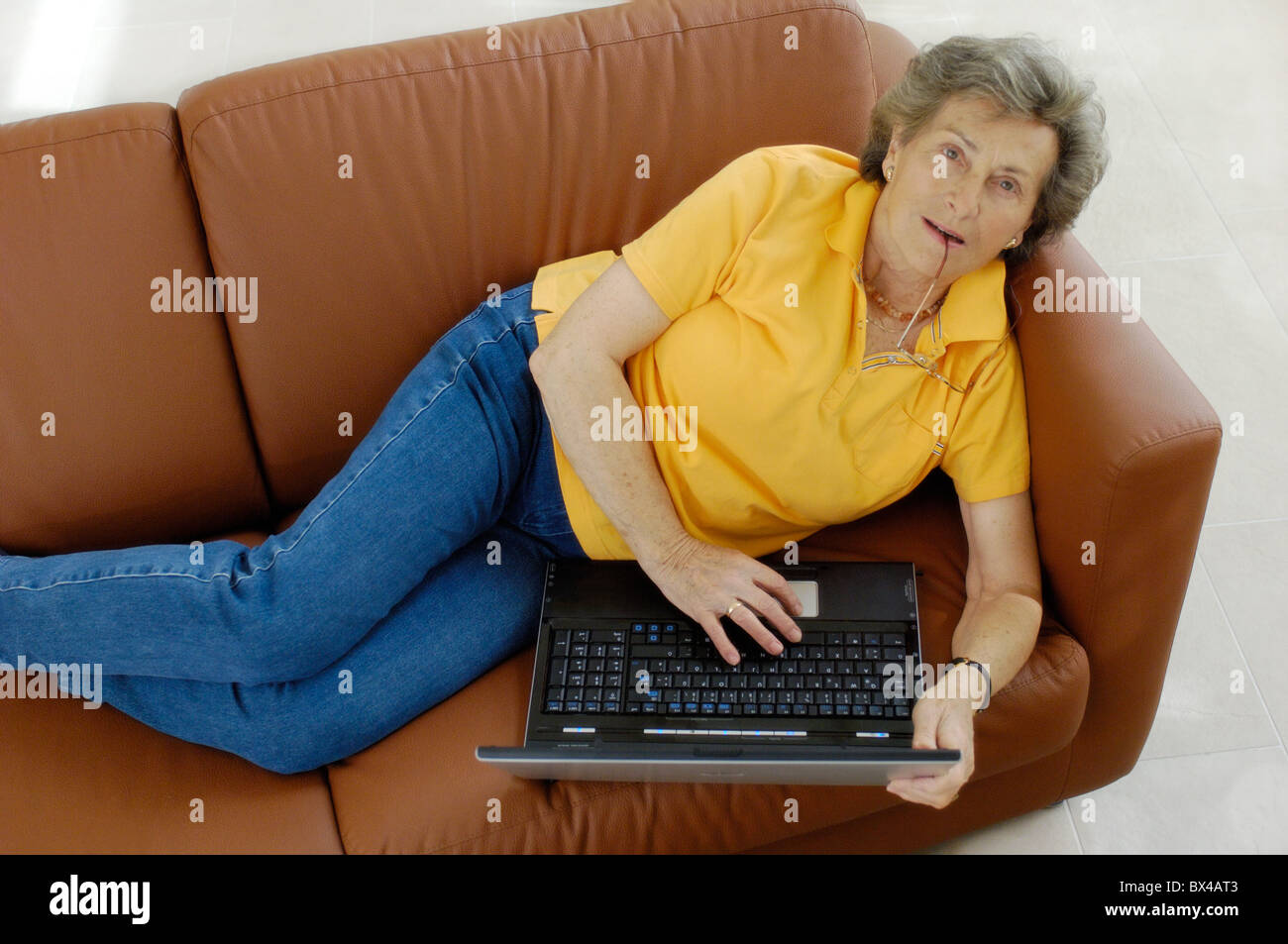 Elderly woman on couch at home with laptop Stock Photo