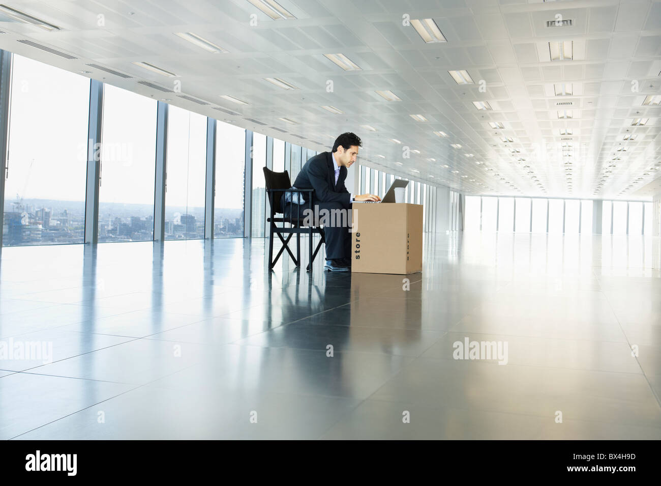Businessman working on laptop in empty office space using cardboard box as desk - Stock Image