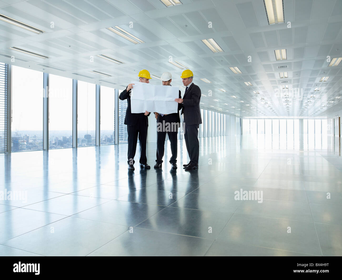 Three executives in hardhats looking at plans in empty office space - Stock Image