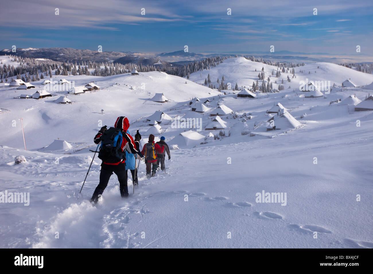 Trekkers descend a hill above shepherds' houses at Velika Planina, Slovenia. - Stock Image