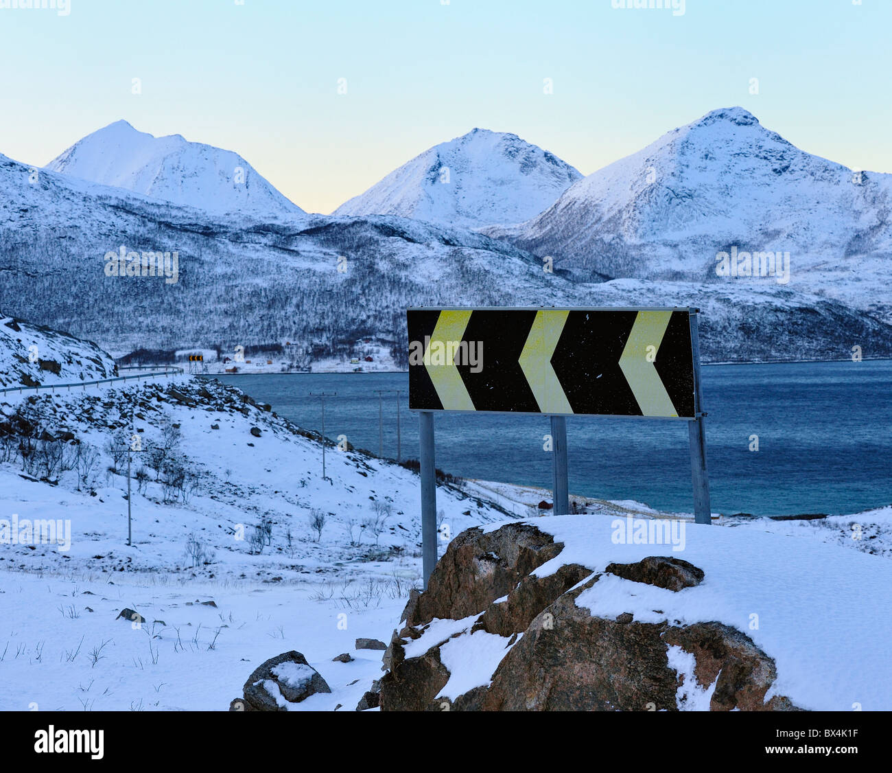 Traffic sign on curvy, narrow winter road in North Norway. - Stock Image
