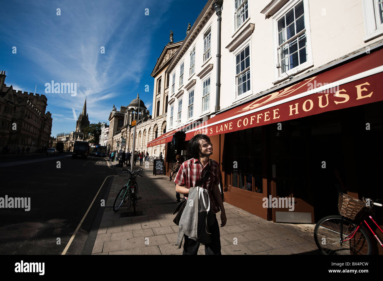 Oxford student enjoying the sun in front of Queen's Lane Coffee House - Stock Image