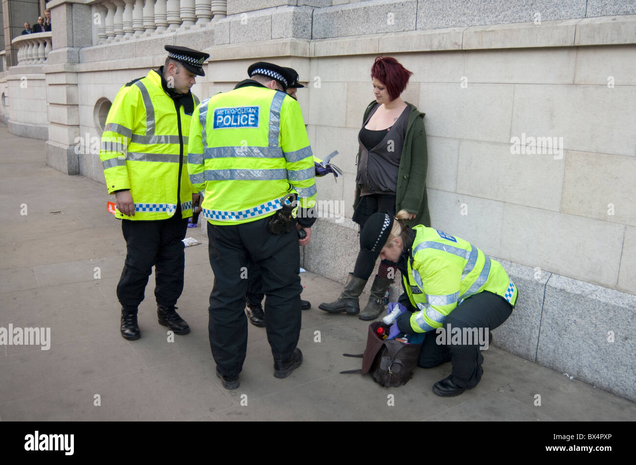 Police search a young woman on the street in London. - Stock Image
