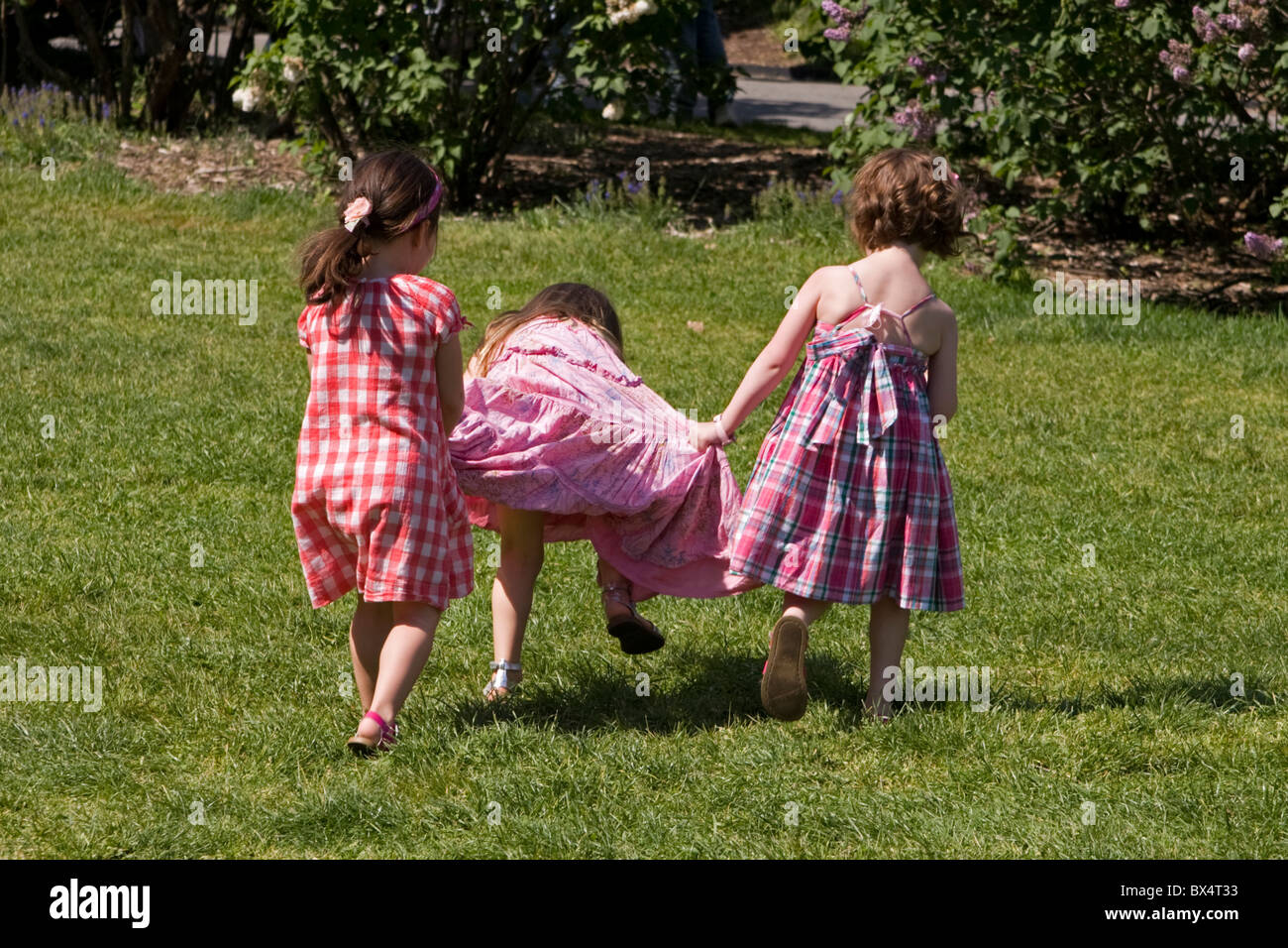 3 small girls find their own amusement at the Botanical Gardens in Brooklyn. - Stock Image