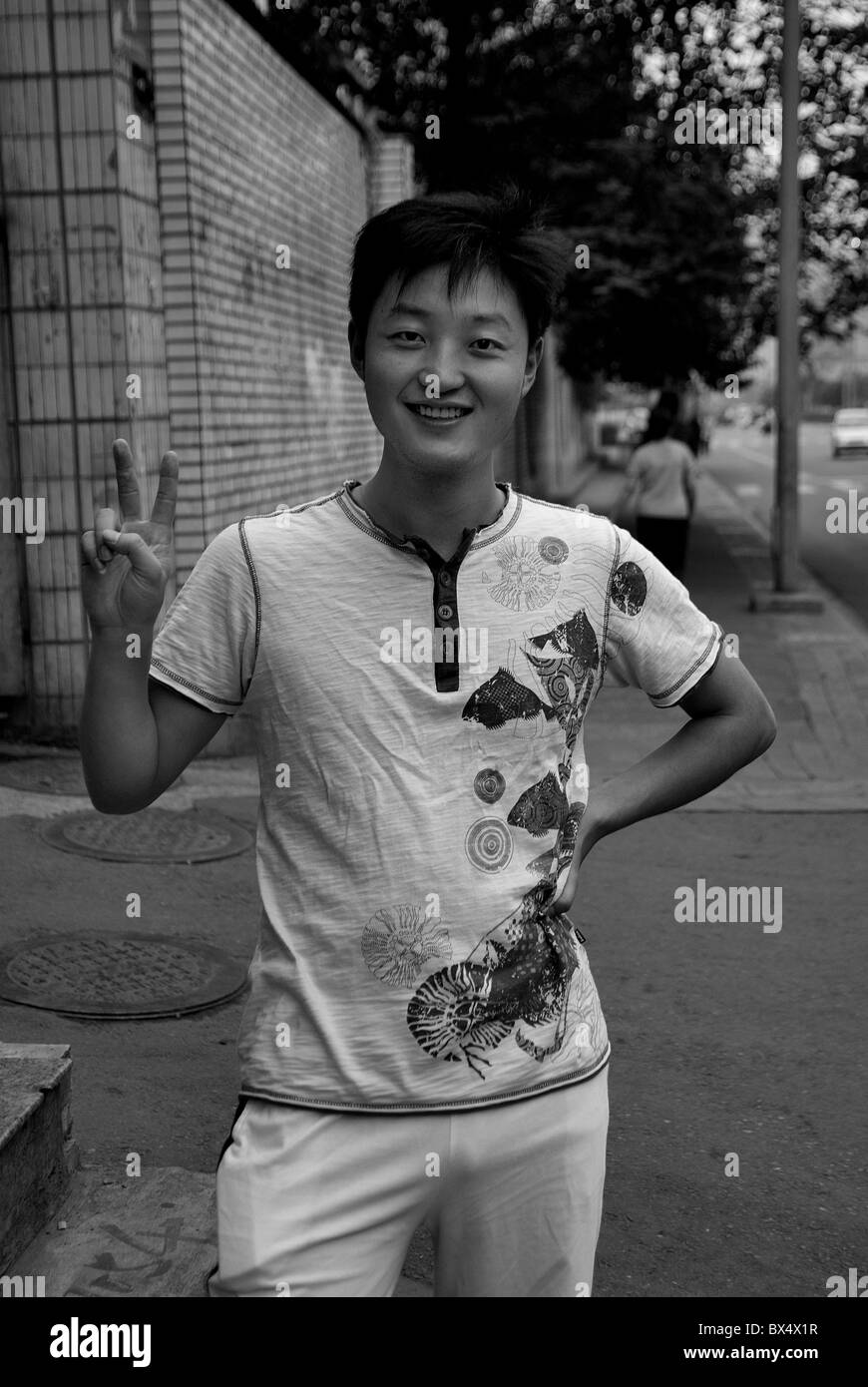 Chengdu - young chinese man posing for photo on the street - Stock Image