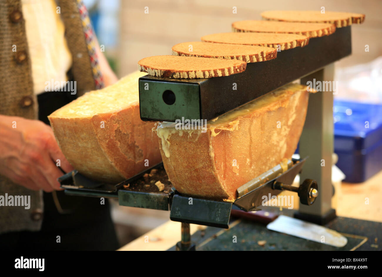 Man melting swiss raclette cheese to put it on toasted brown bread - Stock Image