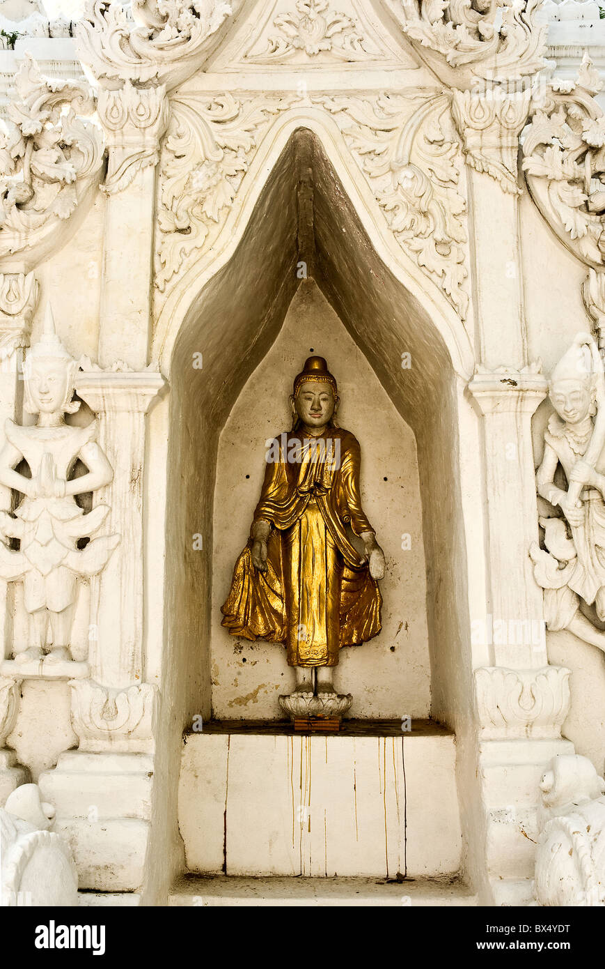 A statue in a recess in a wall at Wat Buppharam in Chiang Mai in Thailand Stock Photo