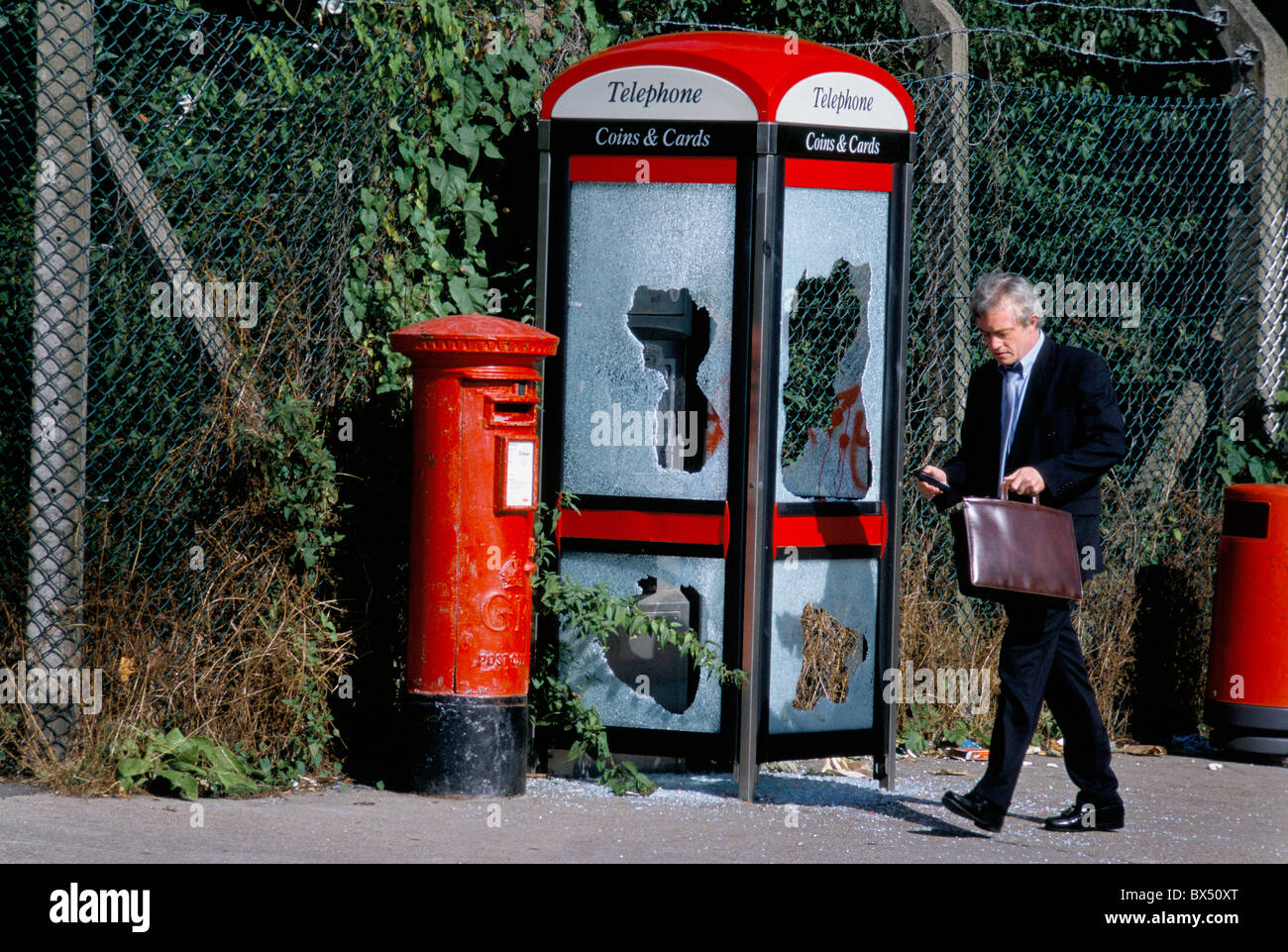 A businessman passing a vandalised British Telecom payphone booth on a South London street. - Stock Image