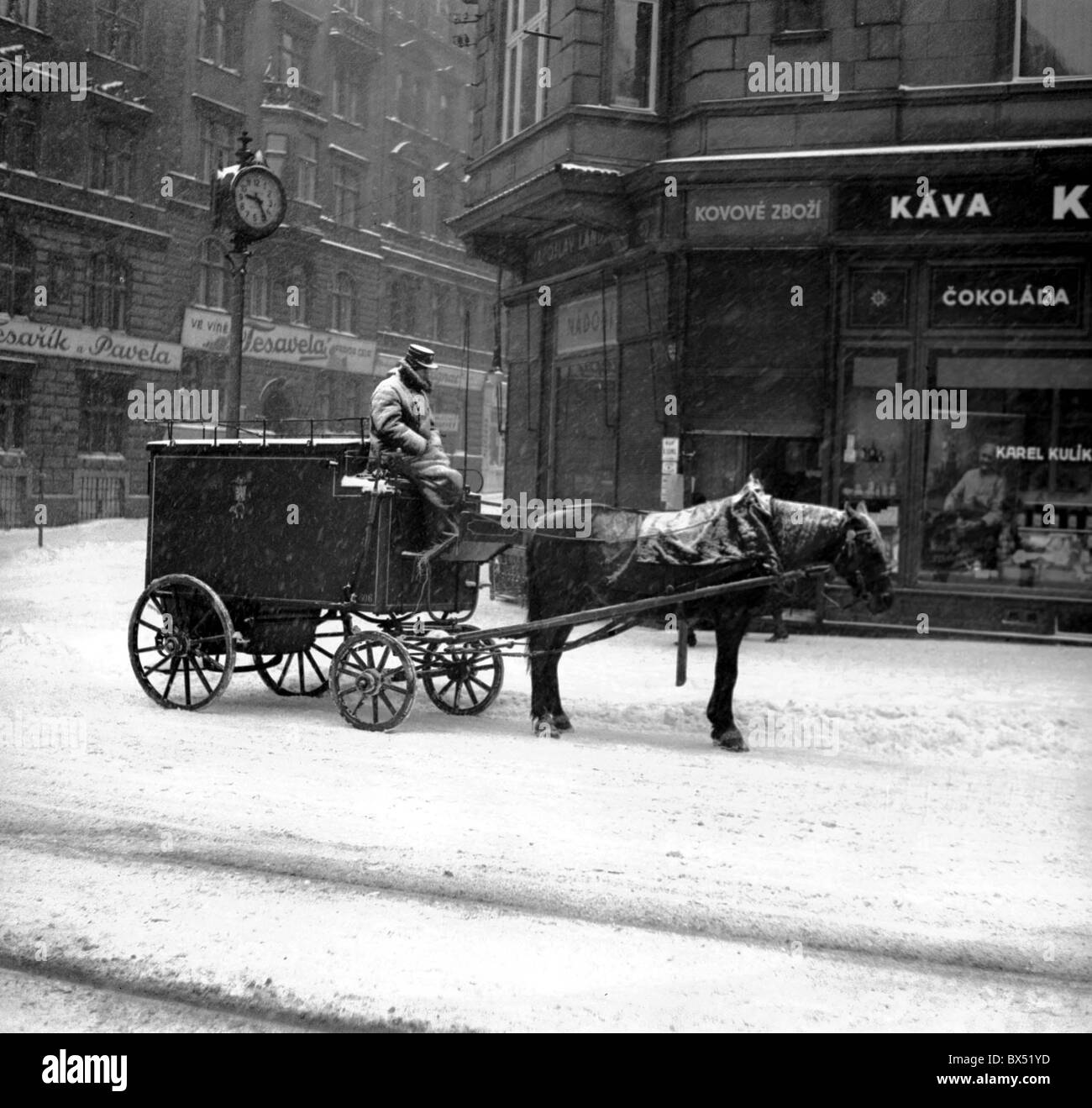 Prague 1937, postal carrier distributes mail in snow covered Prague, horse drawn carriage, fighting weather. - Stock Image