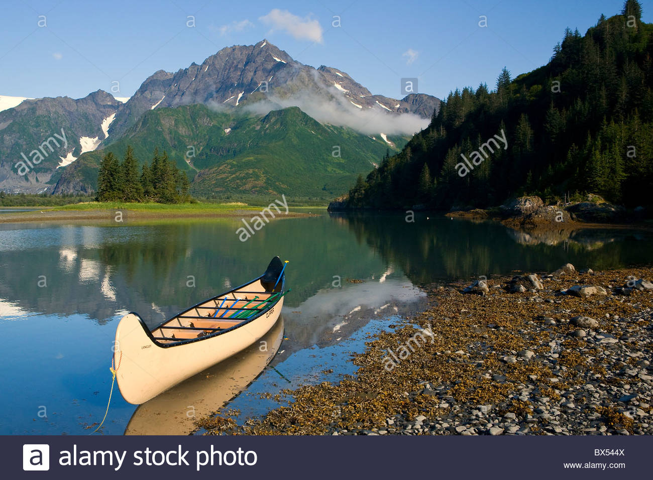 A canoe sits in waiting on a sunny day on the Lower Pedersen Lagoon, Kenai Fjords National Park. - Stock Image