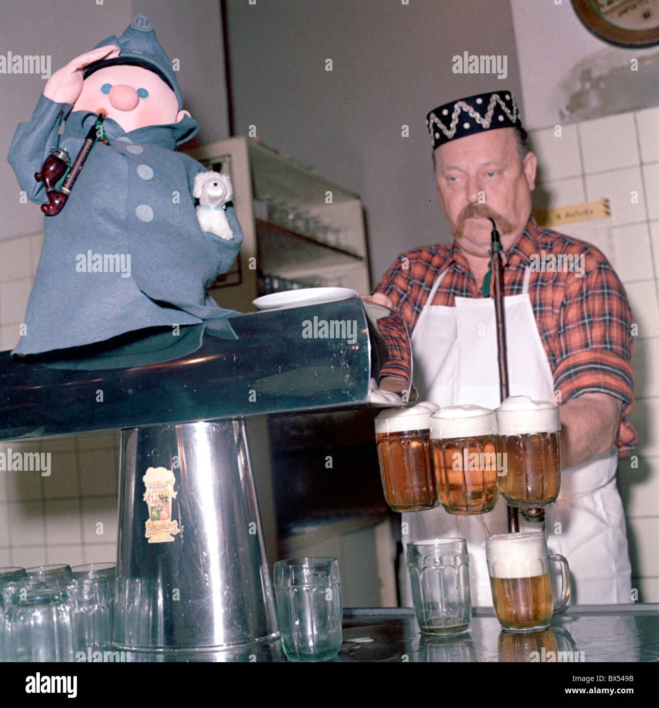 innkeeper, landlord, bartender, draught draft tap beer, glass, pipe, cap, pub, restaurant U Kalicha, Svejk Stock Photo