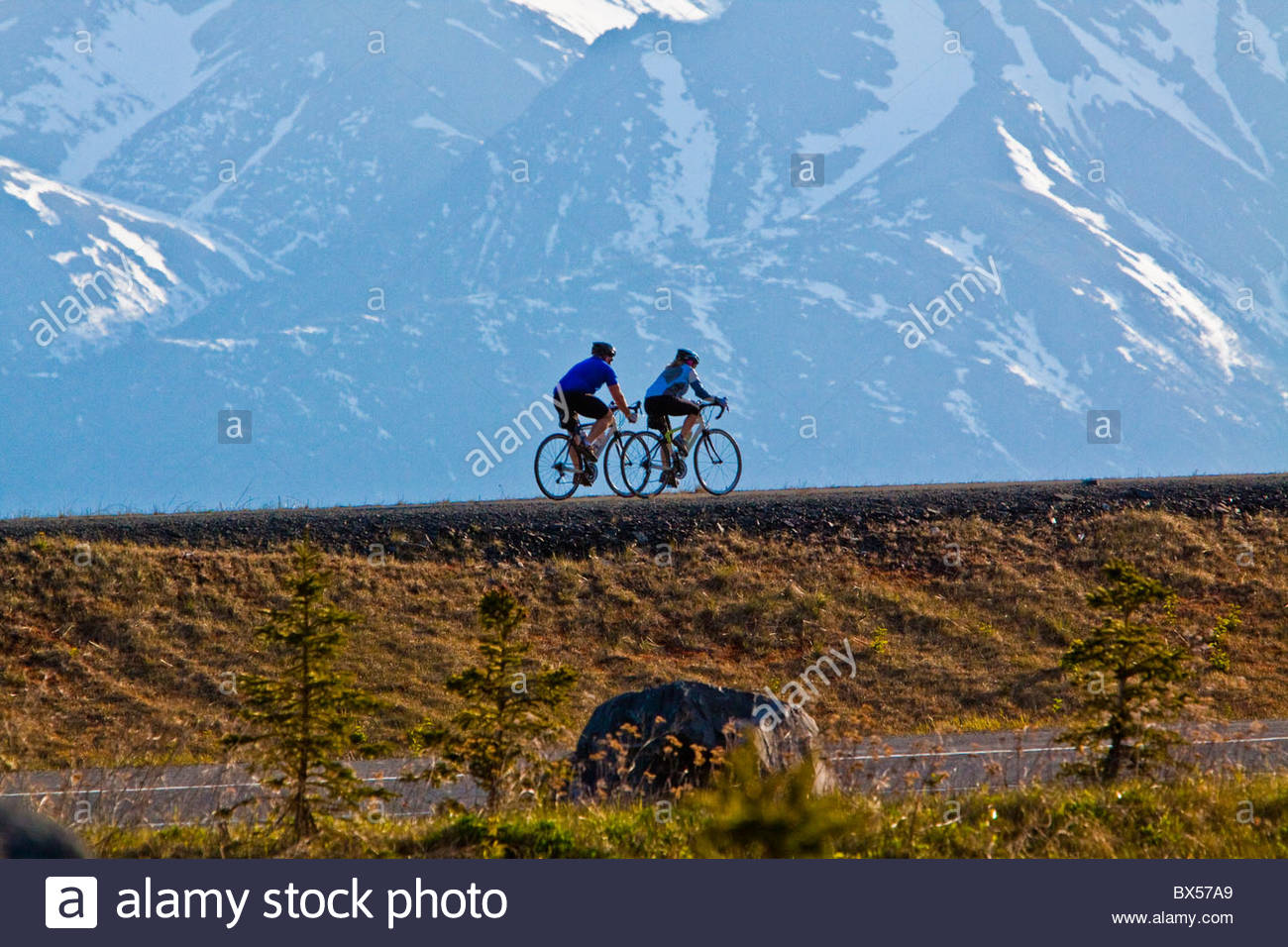 Two bicycle riders on trail along the Turnagain Arm along the Seward Highway with Mountain background. Big Country. - Stock Image
