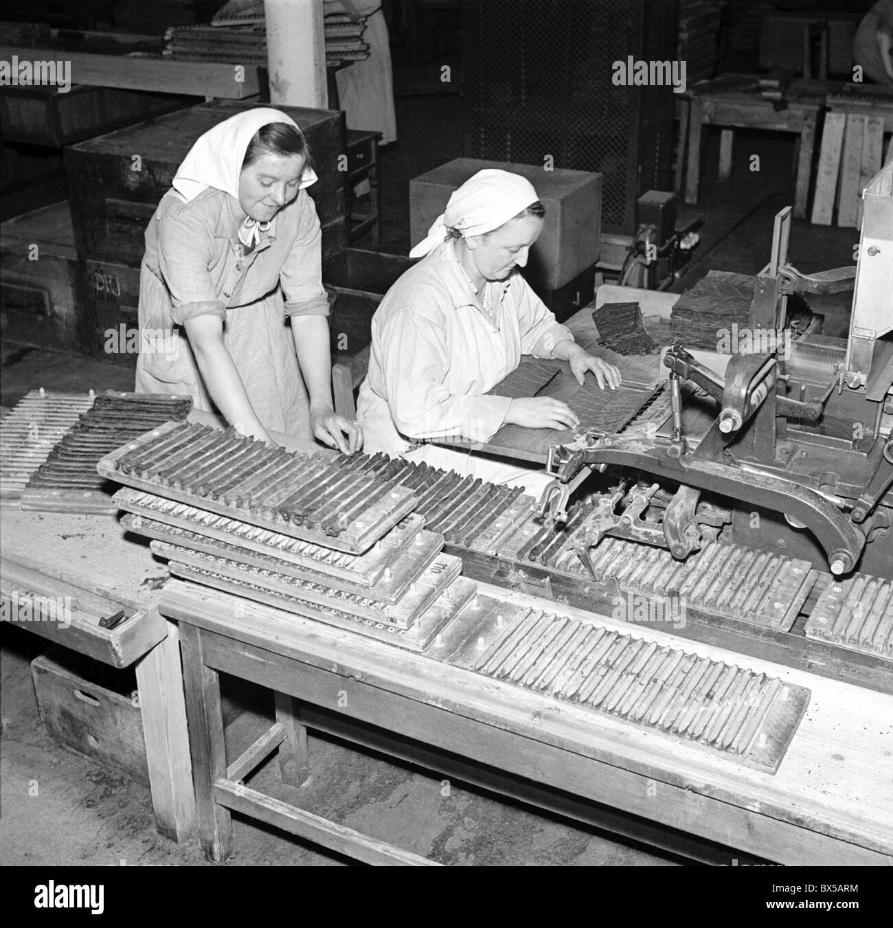 Czechoslovakia - Budweiss 1950.  Tobacco plant workers sort through tobacco leaves and roll cigars. . CTK Vintage - Stock Image