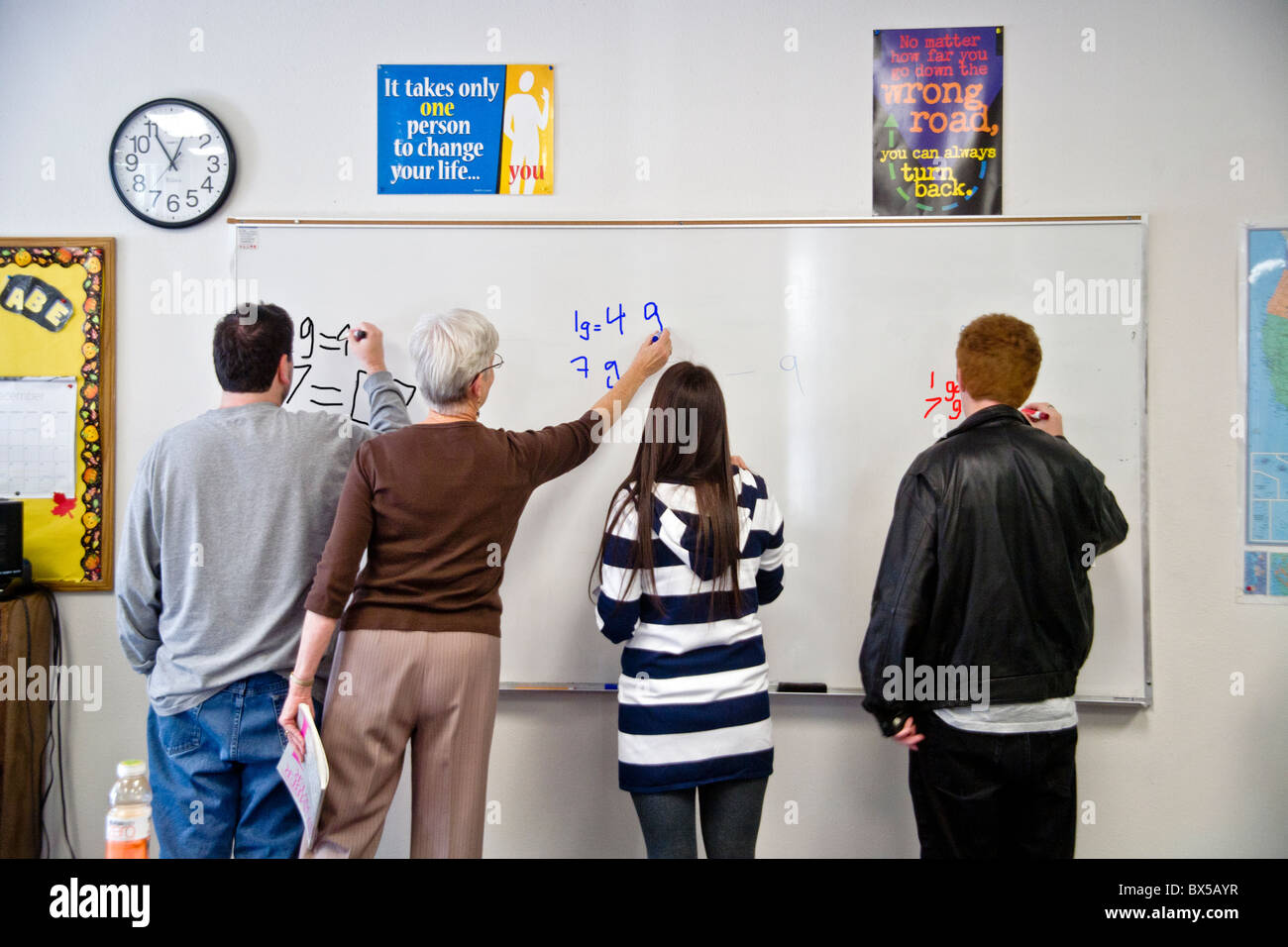 Young adult students and their teacher do math on the whiteboard in ...