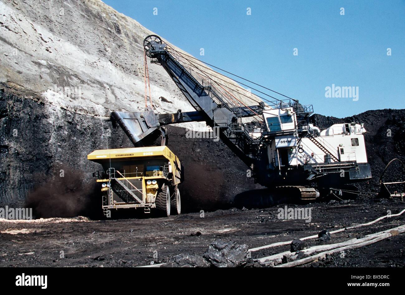 Coal, surface mine, P & H Electric shovel loading rough service dump truck. - Stock Image