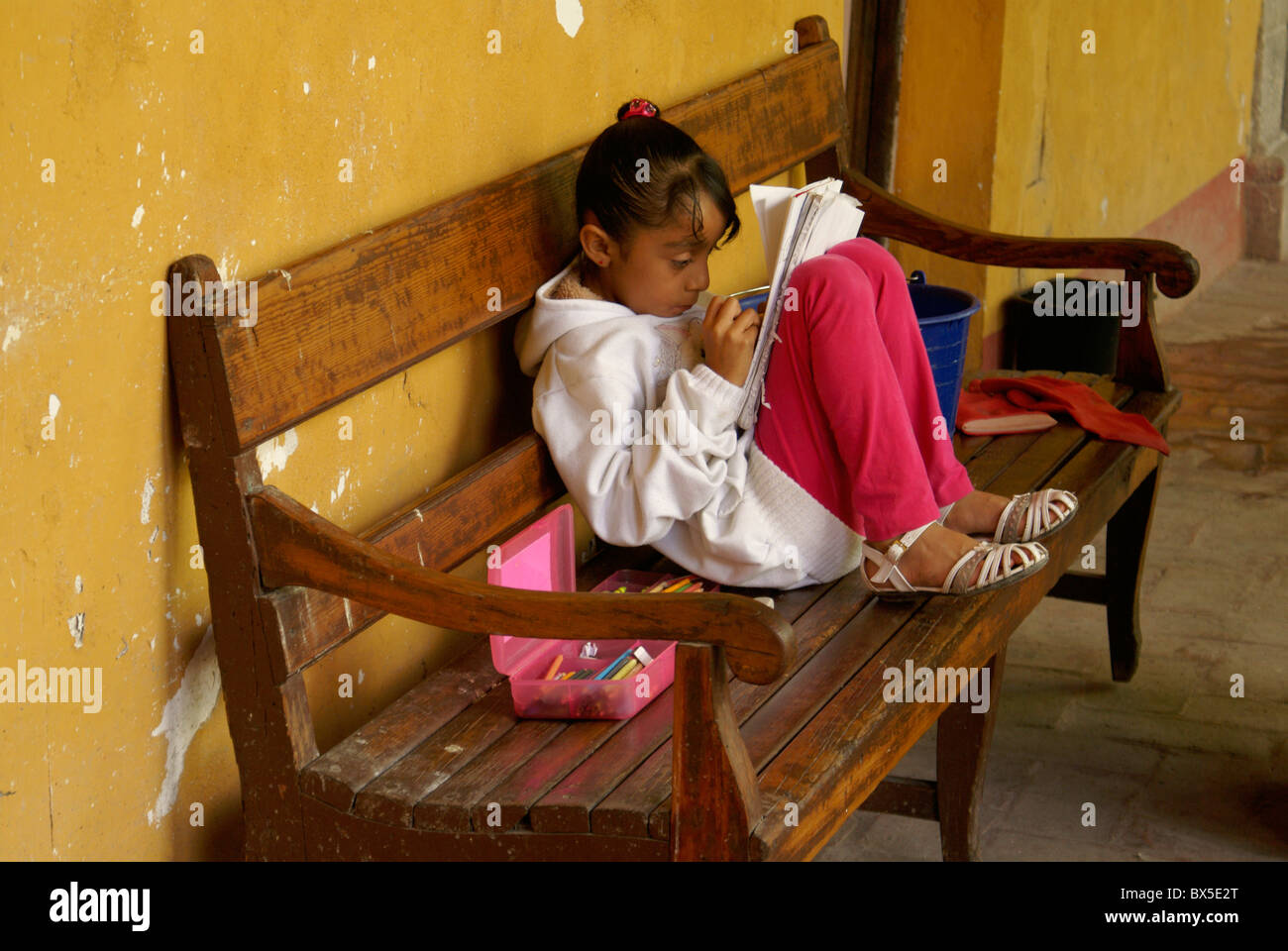 Young girl reading and coloring in San Miguel de Allende, Mexico. San Miguel de Allende is a UNESCO World Heritage - Stock Image