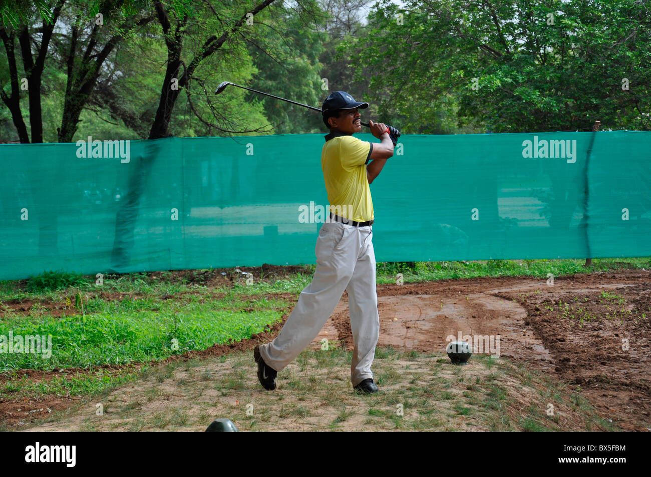 An Indian golfer teeing off - Stock Image