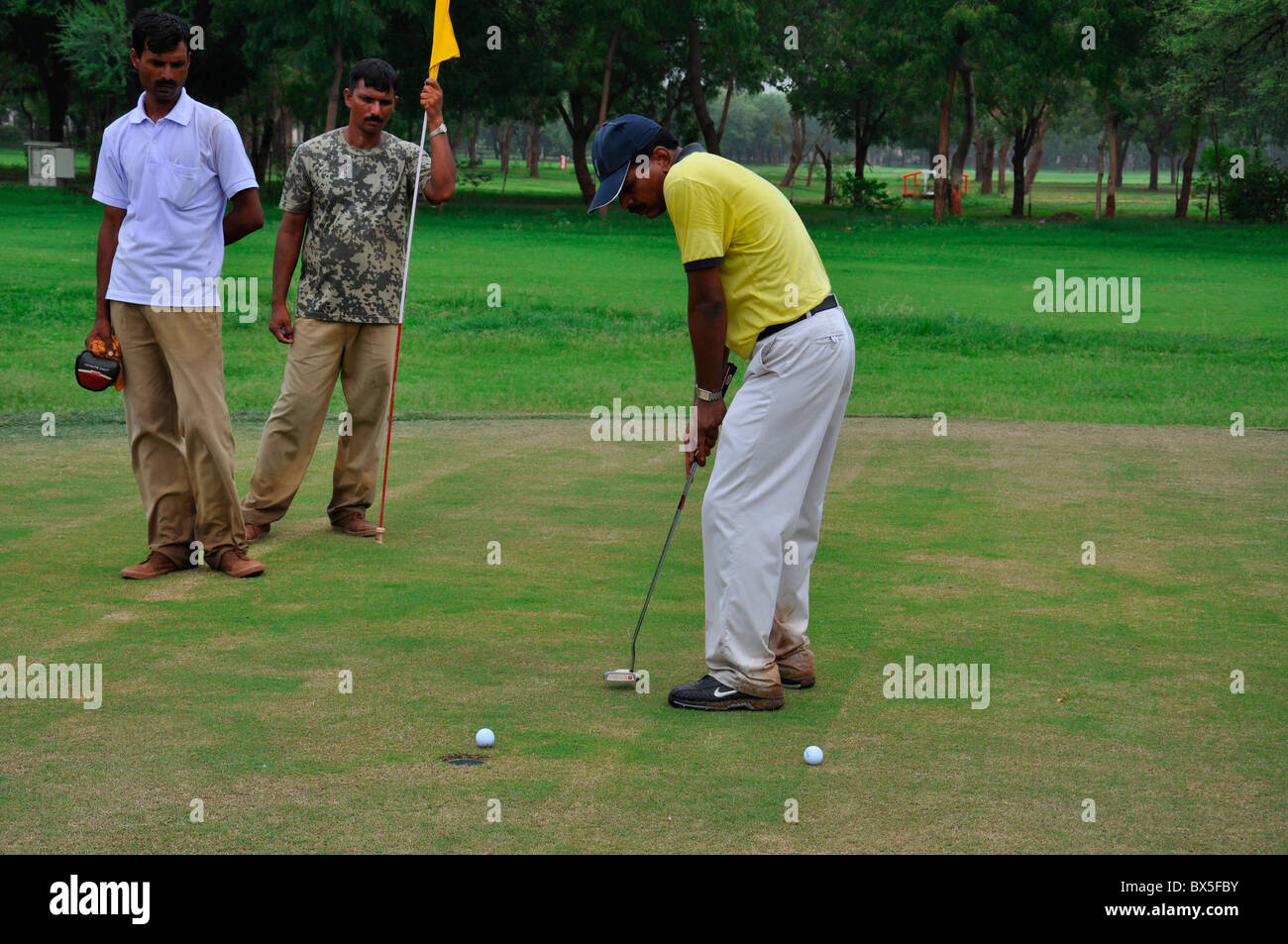 An Indian golfer putting in the green of a golf course - Stock Image