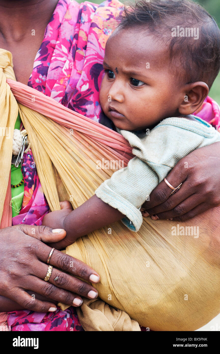 Rural indian baby in mothers sling. India - Stock Image
