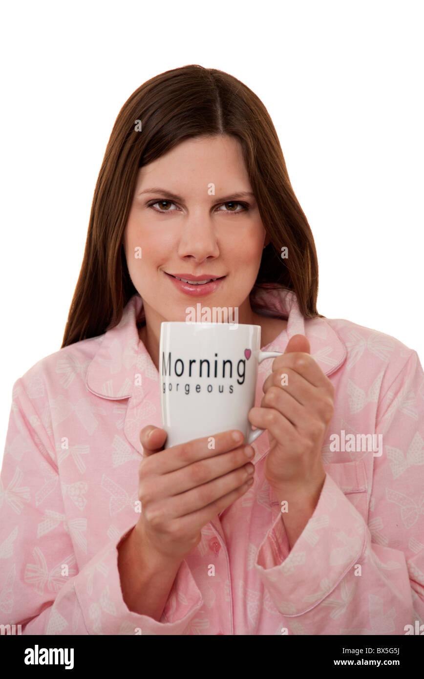 brunette woman holding mug of tea in her pyjamas Stock Photo