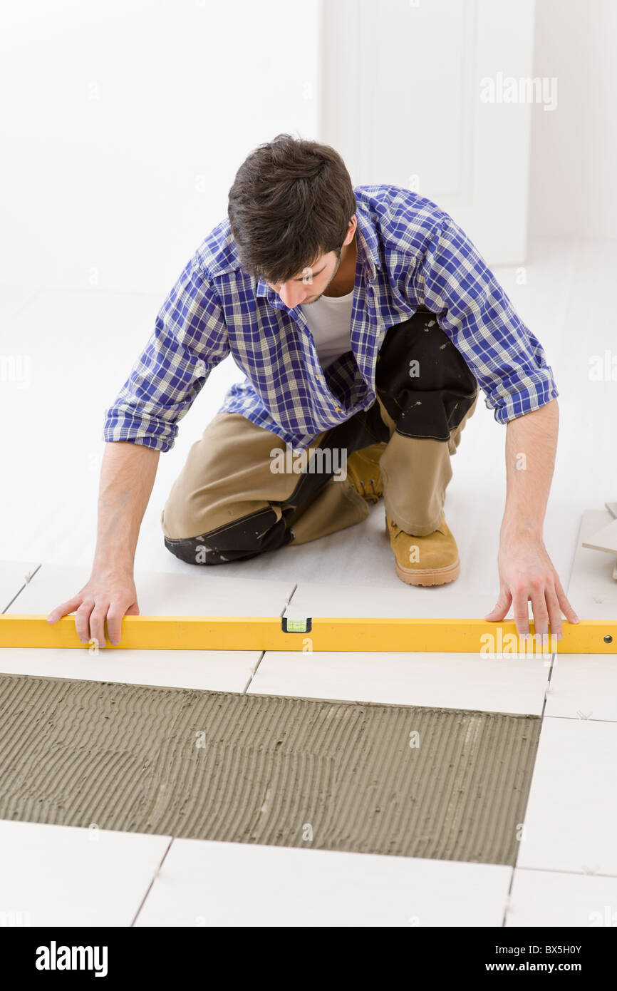 Tile floor stock photos tile floor stock images alamy home tile improvement handyman with level laying down tile floor stock image dailygadgetfo Choice Image