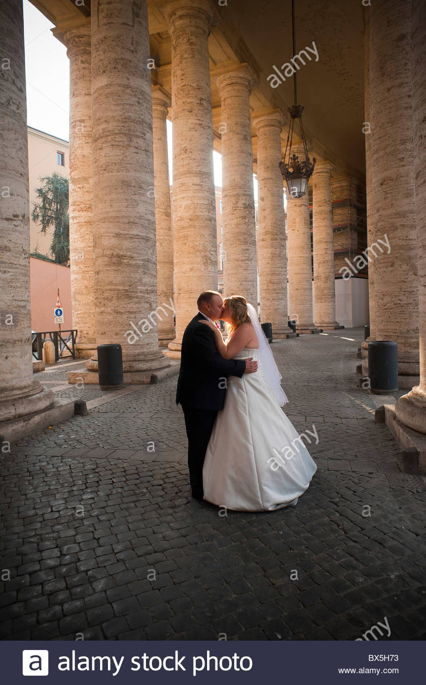 Newlyweds kissing underneath the Colonnade of Saint Peter's square - Stock Image