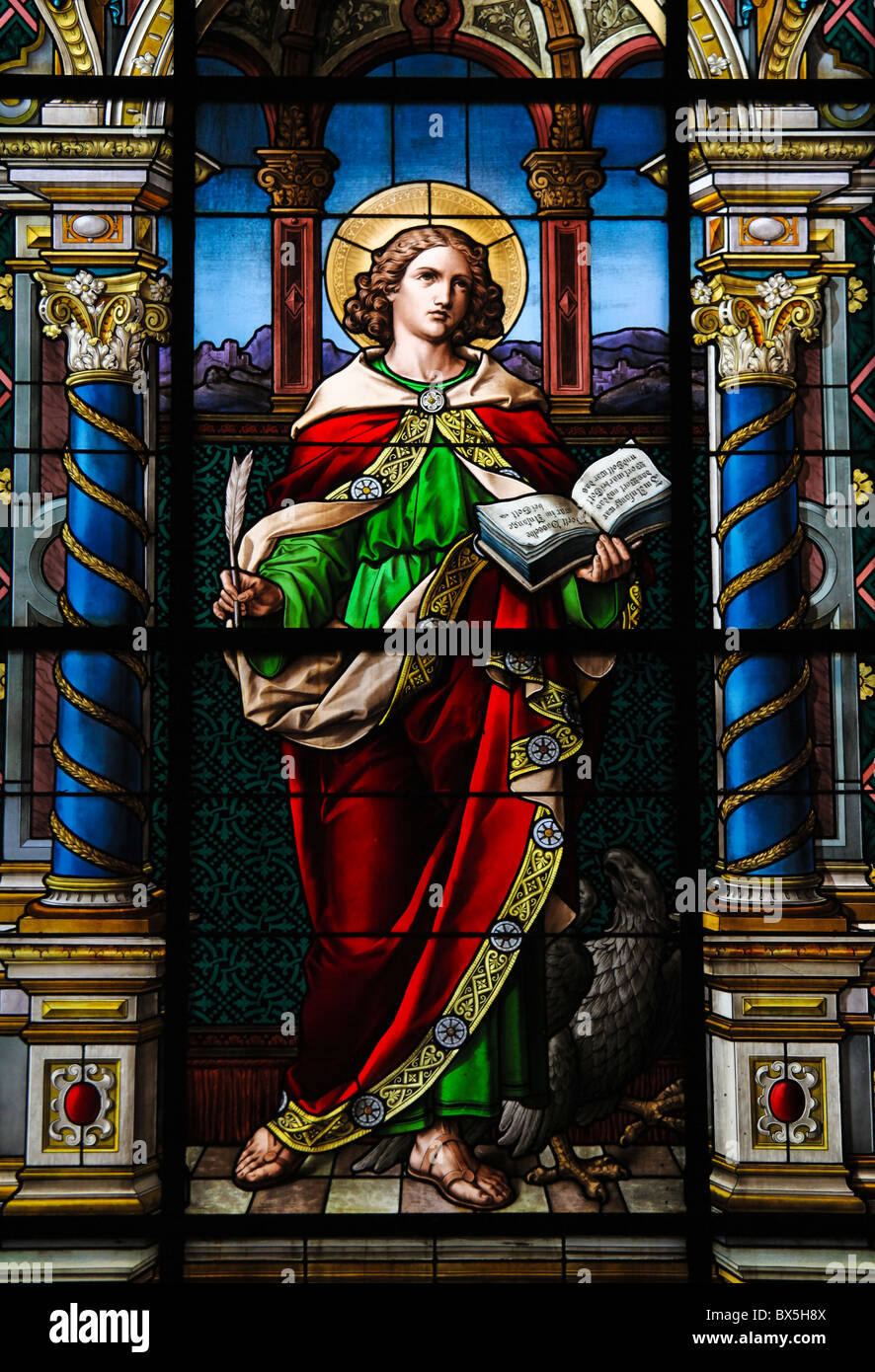 Saint John the Evangelist. Stained glass window created by F. Zettler (1878-1911) at the German Church (St. Gertrude's Stock Photo