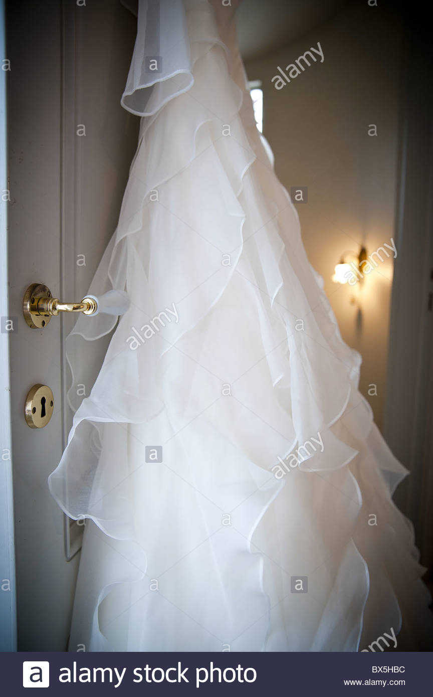 Bridal wedding dress hanging from a door - Stock Image