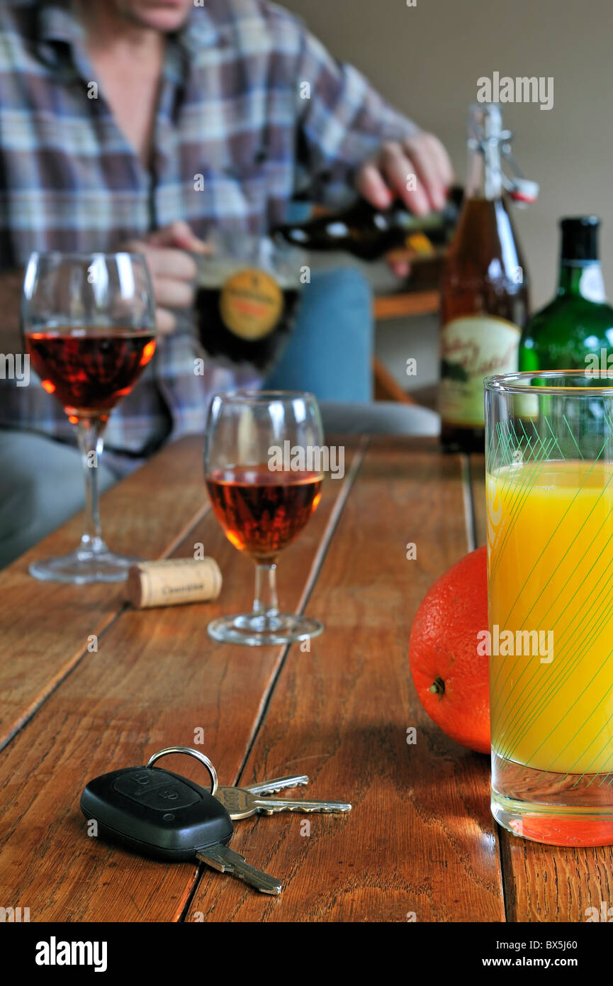 Car key, drunken man pouring beer, fruit juice and alcoholic drinks on table to illustrate responsible driving Stock Photo