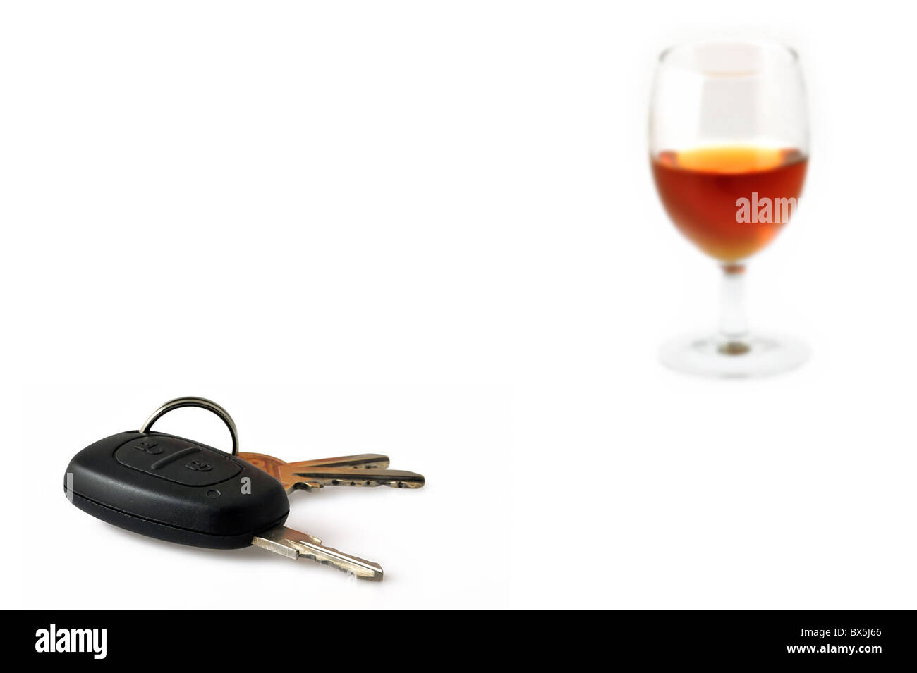 Car key and glass filled with alcohol as conceptual subjects to illustrate irresponsible driving Stock Photo