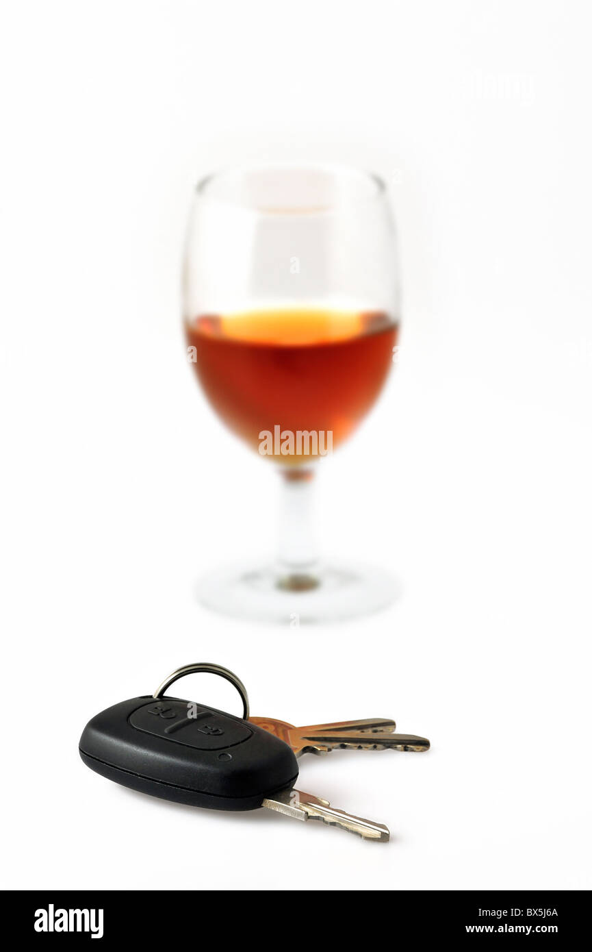 Car key and glass filled with alcohol as conceptual subjects to illustrate irresponsible driving - Stock Image