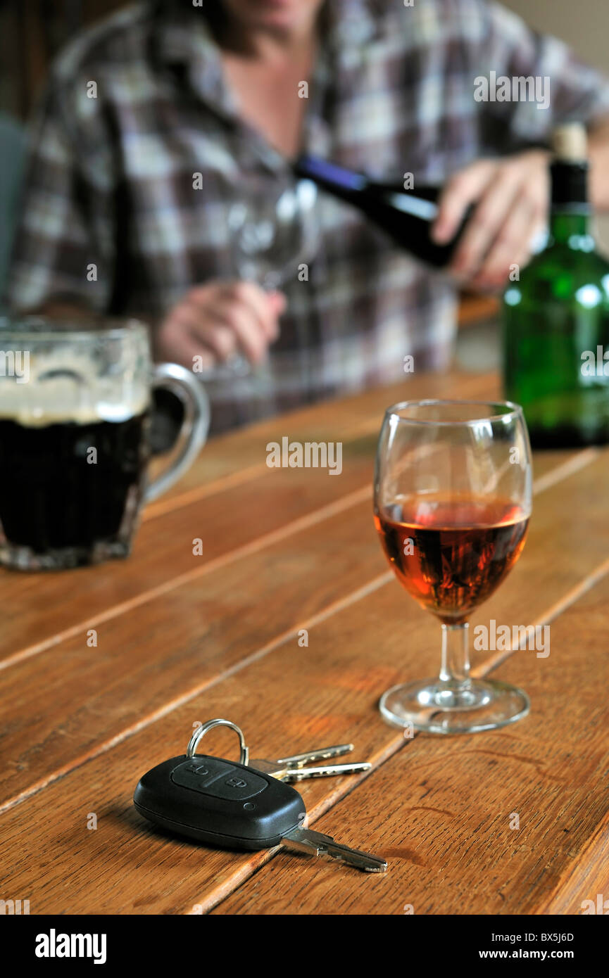 Car key, drunken man pouring wine and alcoholic drinks on table to illustrate irresponsible driving Stock Photo