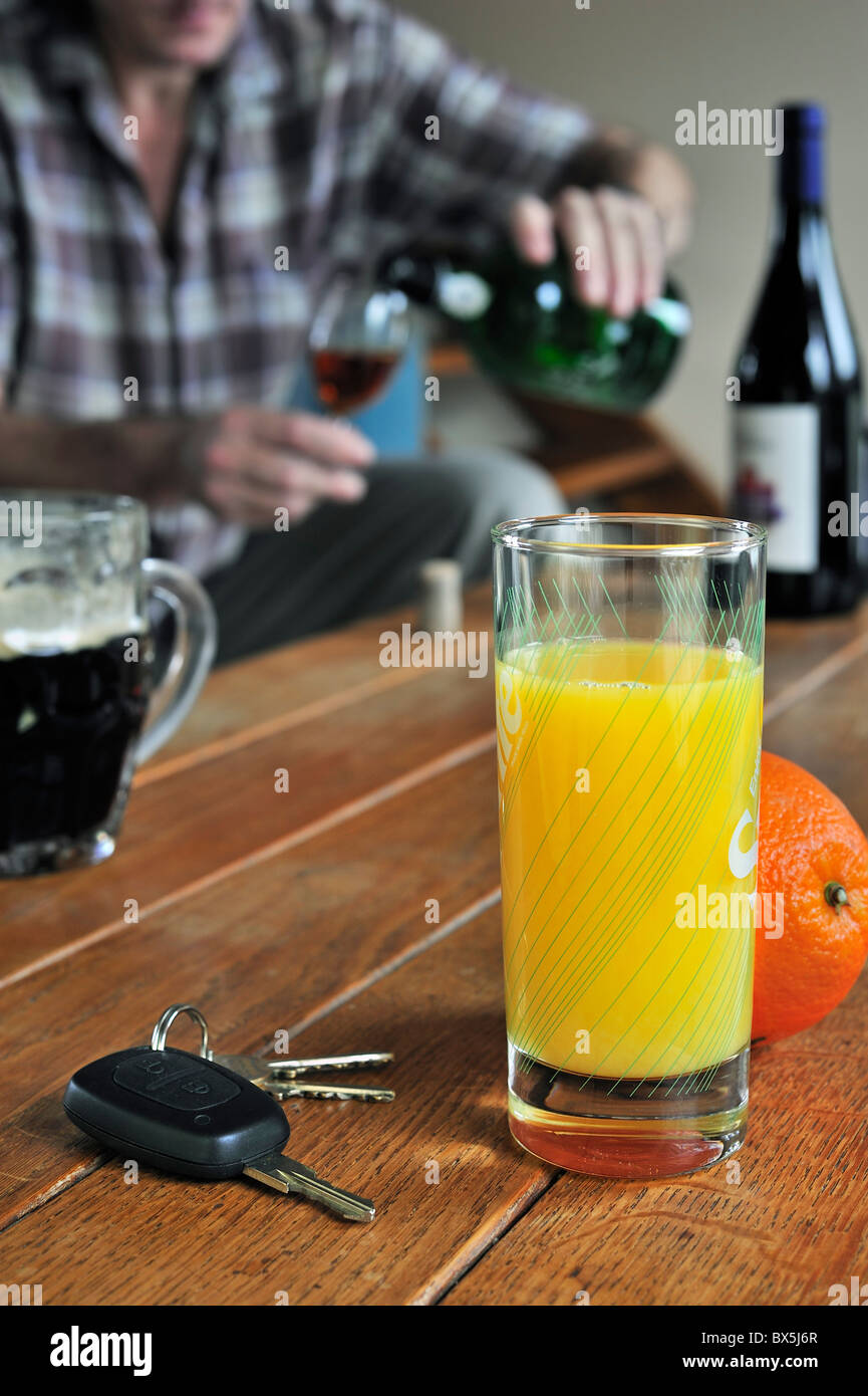 Car key, drunken man pouring wine, alcoholic drinks and soft drink on table to illustrate responsible driving Stock Photo