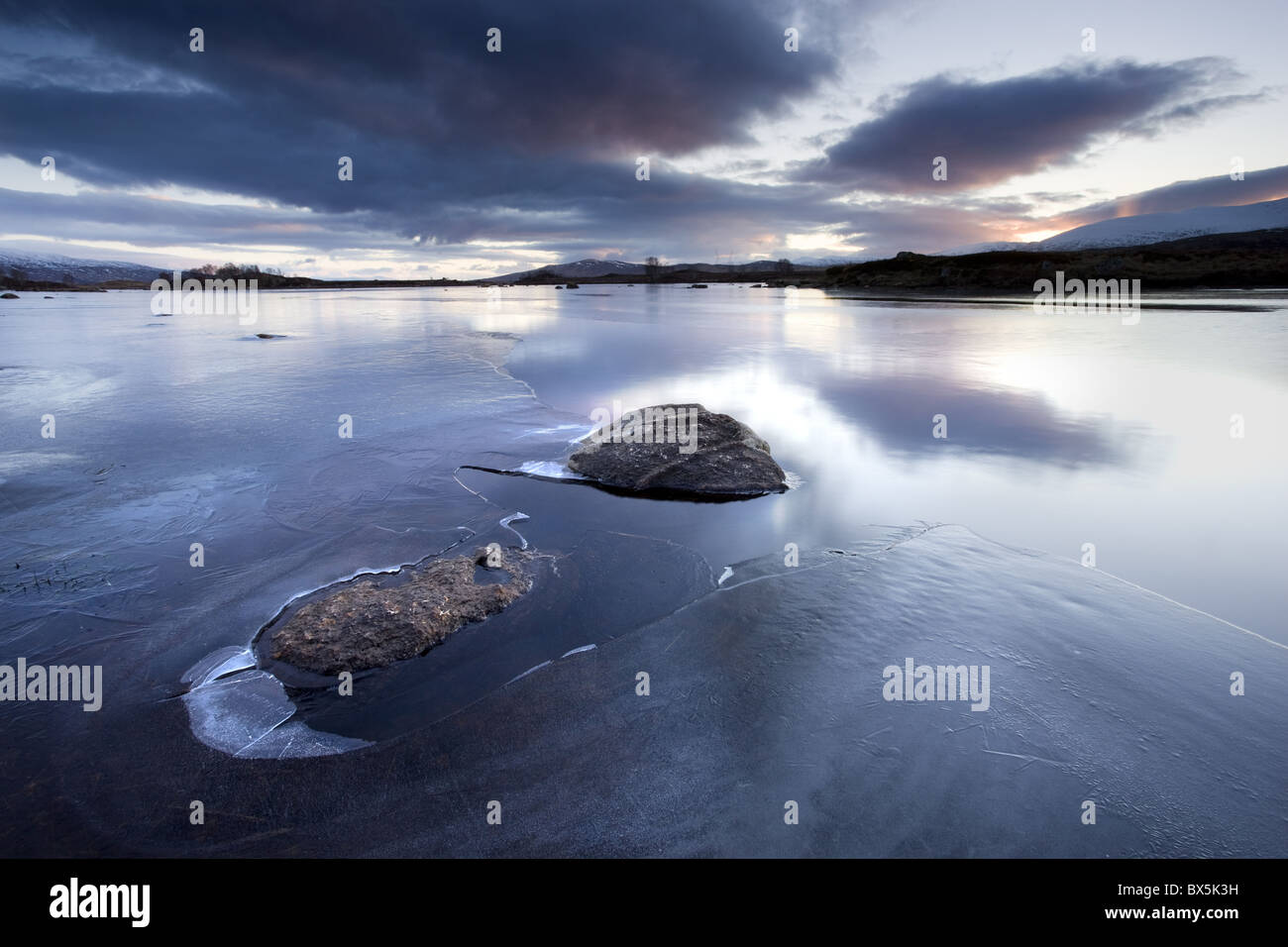 Winter view of Loch Ba' at dawn, loch partly frozen with two large rocks protruding from the iceg, Rannoch Moo, - Stock Image