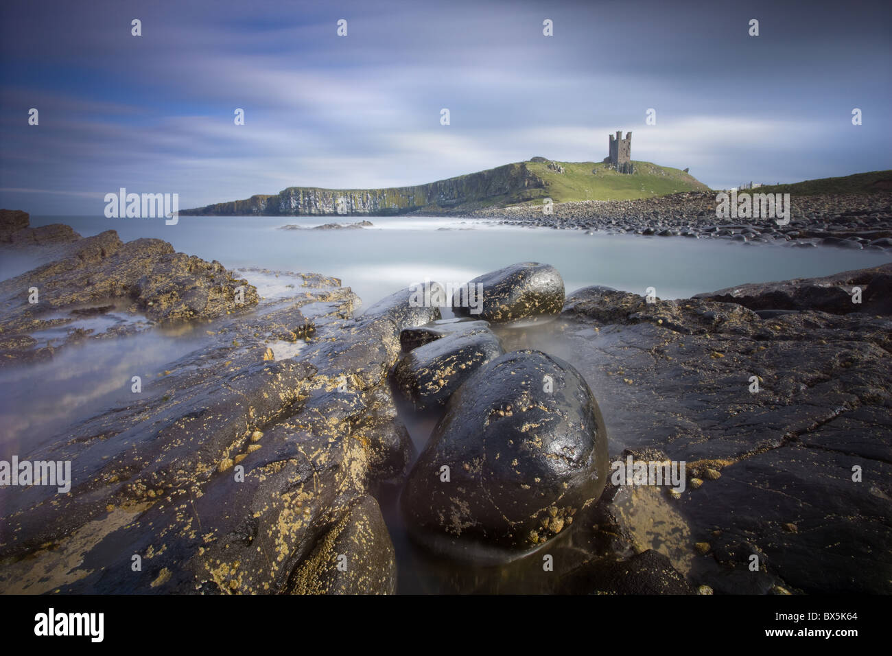 Dunstanburgh Castle bathed in afternoon sunlight with rocky coastline in foreground, Embleton Bay, Northumberland, Stock Photo