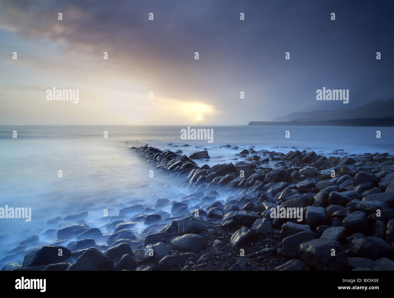 Sunset on stormy winter's day looking across Kimmeridge Bay from the remains of Clavell's Pier, Kimmeridge, - Stock Image