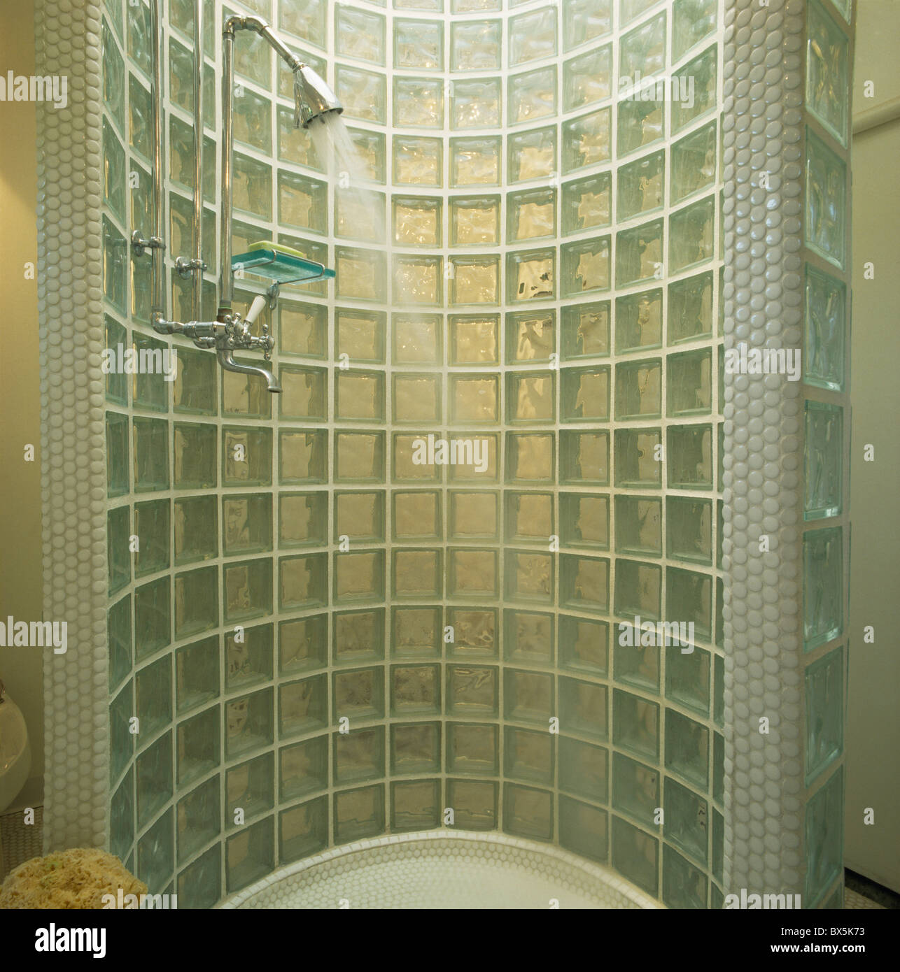 Water Pouring From Chrome Shower In Curved Glass Brick Cabinet