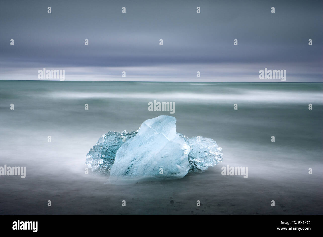Piece of glacial ice washed ashore by the incoming tide near glacial lagoon at Jokulsarlon, Iceland, Polar Regions - Stock Image