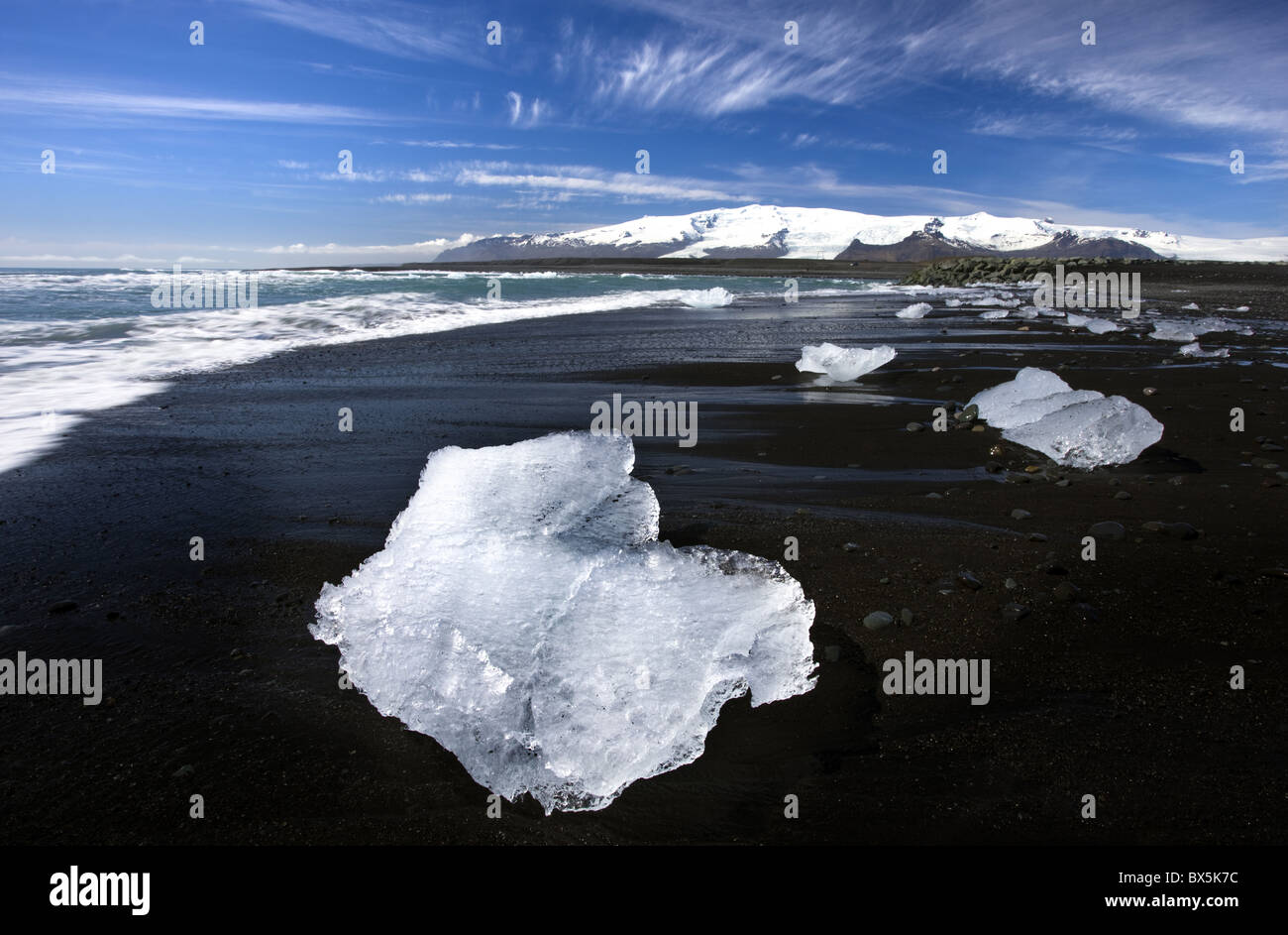 Piece of glacial ice washed ashore by the incoming tide onto beach of volcanic sand near glacial lagoon at Jokulsarlon, - Stock Image