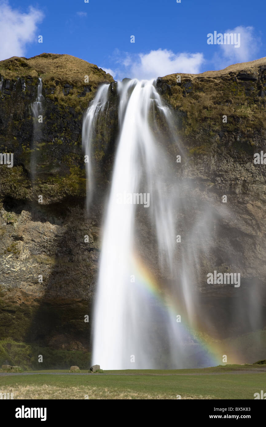 Seljalandsfoss Waterfall tumbling over towering cliffs in bright sunlight with rainbow at the base of the waterfall, - Stock Image