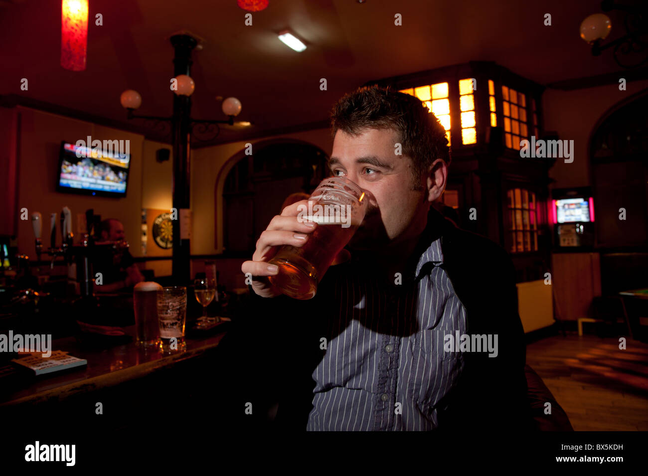 A man drinking a pint of beer in a pub, UK - Stock Image